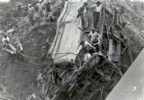 Railroad workers cutting through train wreckage